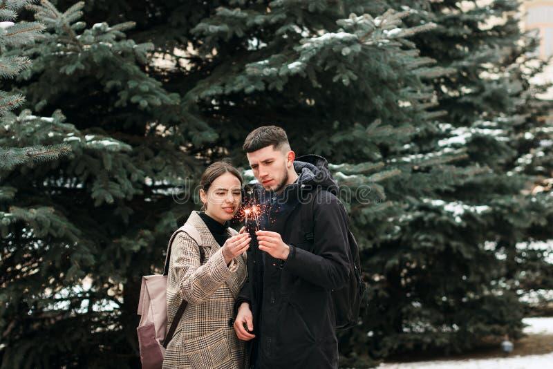 Le jeune couple romantique a l'amusement dehors en hiver avant Noël avec des lumières de Bengale images stock