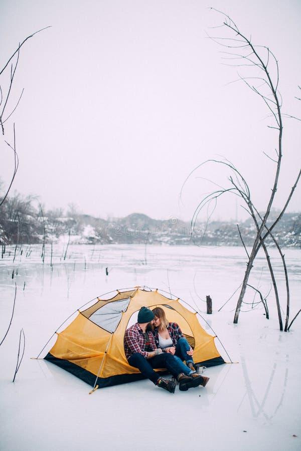 Le jeune couple se repose dans la tente pendant la hausse d'hiver sur le fond de neige images libres de droits