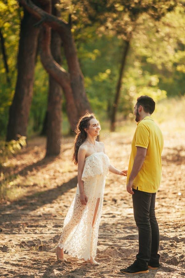 Le jeune couple sourit et tient des mains dans la forêt image stock