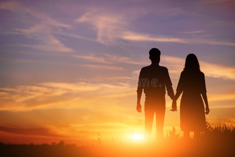 Le jeune couple tient des mains sur une silhouette de coucher du soleil de fond photographie stock