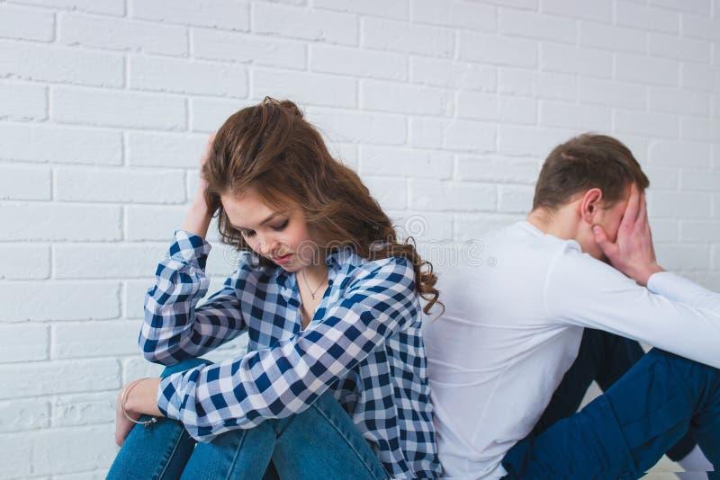 Le jeune couple triste se repose de nouveau au dos sur le divan à la maison ayant une querelle photo libre de droits