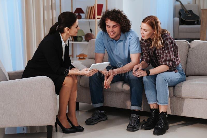 Le jeune couple veut ? acheter une maison qu'ils ont une conversation avec le vrai agent immobilier observant par le comprim? photos libres de droits