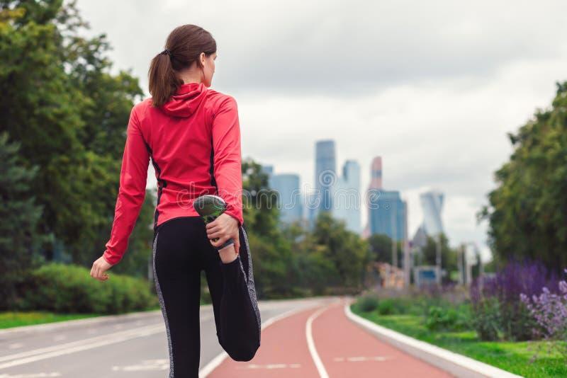Le jeune coureur de femme de forme physique étire ses jambes avant de courir dehors images stock