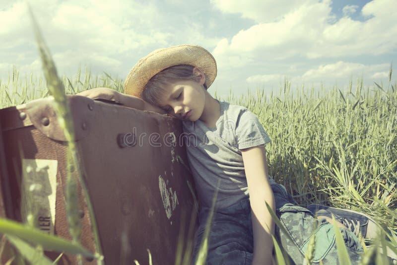 Le jeune cowboy détend au-dessus de sa valise lourde dans un pré image stock