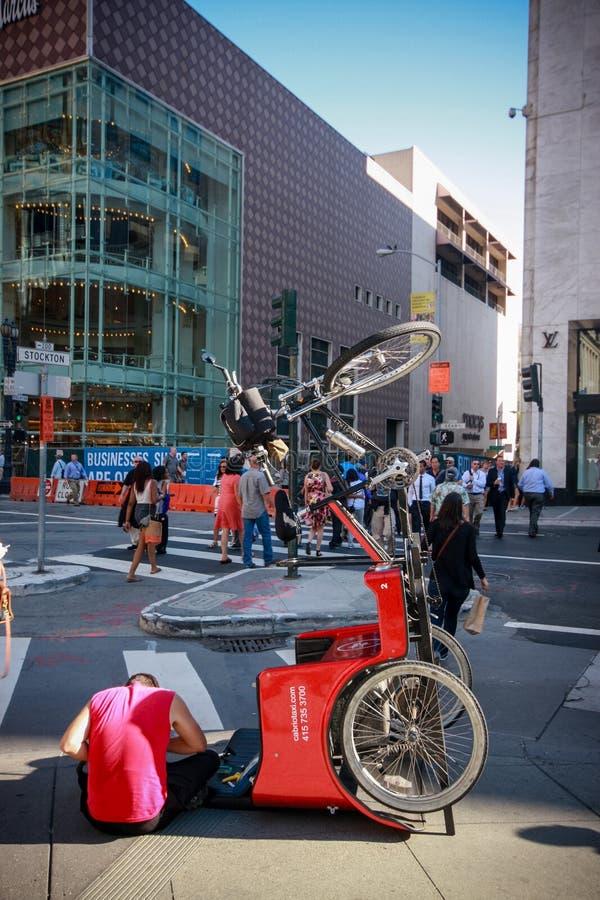 Le jeune cycliste répare le tricycle de touristes à la rue image stock