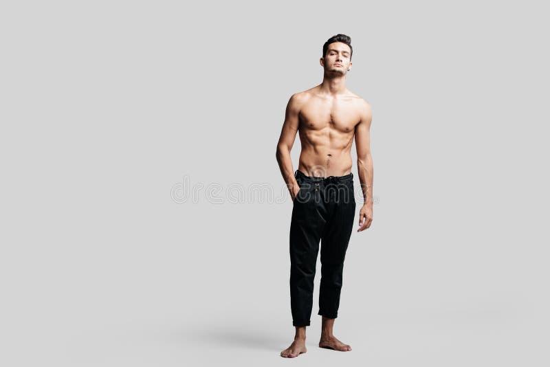 le jeune danseur beau aux cheveux fonc?s avec le port nu de torse pantalon noir de sports se tient avec sa main dans des ses poch images libres de droits