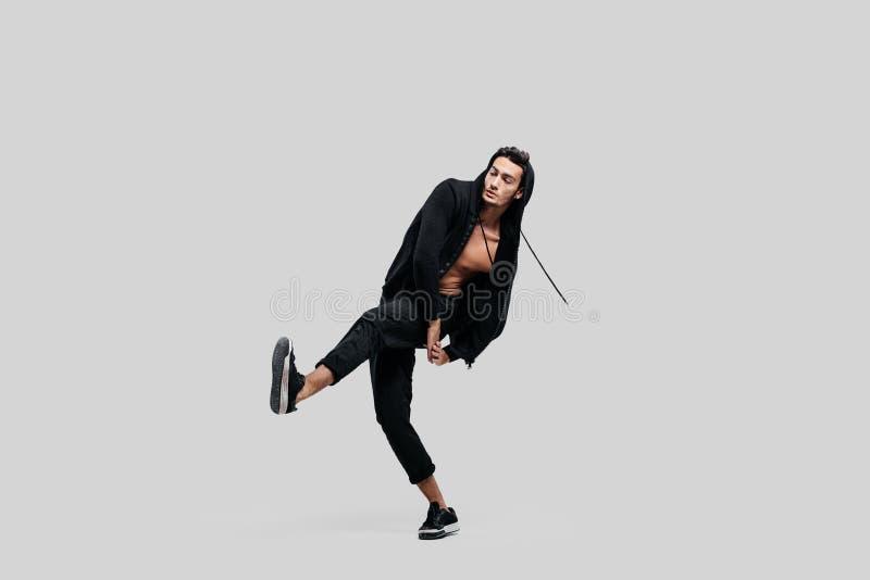 Le jeune danseur beau habill? dans le pantalon noir, un pull molletonn? sur un torse nu soul?ve une jambe tout en dansant la dans photos libres de droits