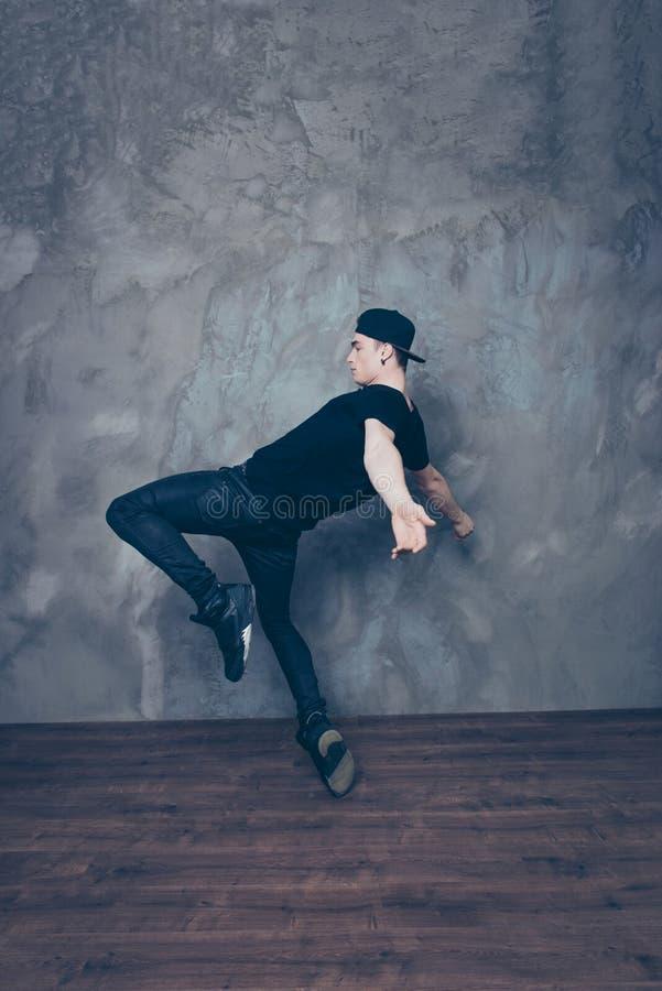Le jeune danseur moderne pose sur un fond de studio tandis que danci photographie stock libre de droits