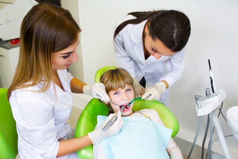 Le jeune dentiste beau traite l'enfant de dent, une dentiste de femme images libres de droits