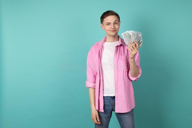 Le jeune directeur beau dans la position rose de chemise avec l'argent remet dedans le mur bleu photo libre de droits