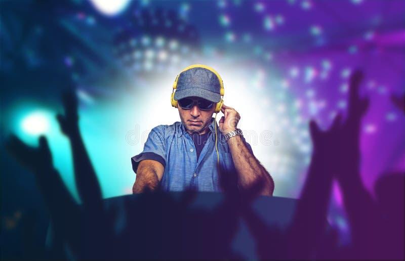 Le jeune DJ heureux et frais jouant la musique à l'événement de partie dans des chansons de mélange de techno de boîte de nu image stock