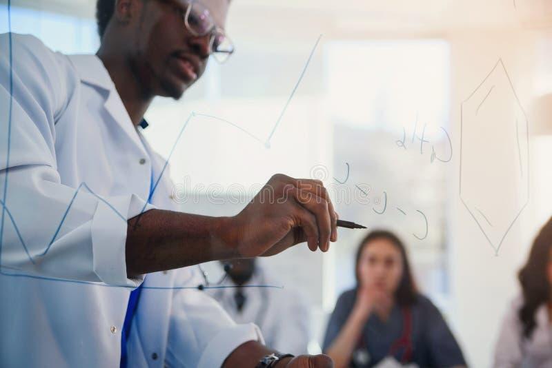 Le jeune docteur africain masculin dessine la formule moléculaire sur le conseil de verre Un professeur dans un laboratoire écriv photos libres de droits