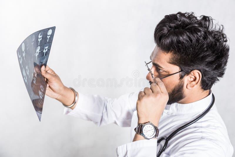 Le jeune docteur beau dans un manteau blanc avec un st?thoscope v?rifie attentivement le rayon X du patient images libres de droits