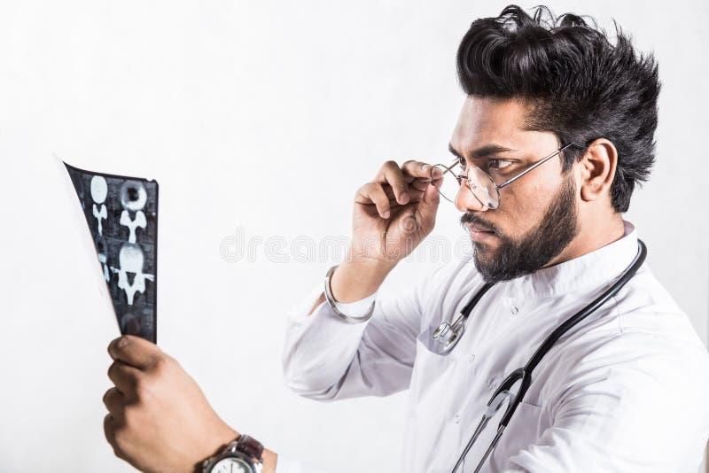 Le jeune docteur beau dans un manteau blanc avec un st?thoscope v?rifie attentivement le rayon X du patient photographie stock