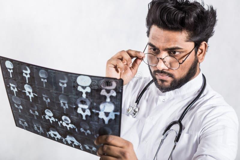 Le jeune docteur beau dans un manteau blanc avec un st?thoscope v?rifie attentivement le rayon X du patient image libre de droits