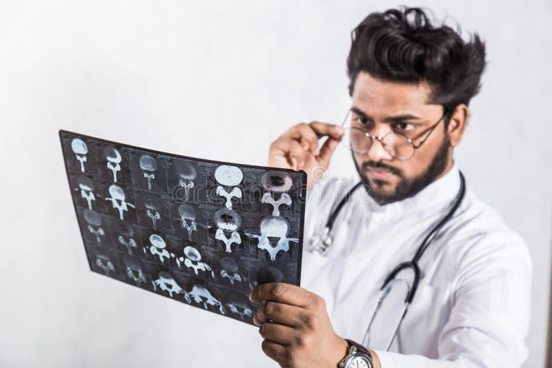 Le jeune docteur beau dans un manteau blanc avec un st?thoscope v?rifie attentivement le rayon X du patient images stock