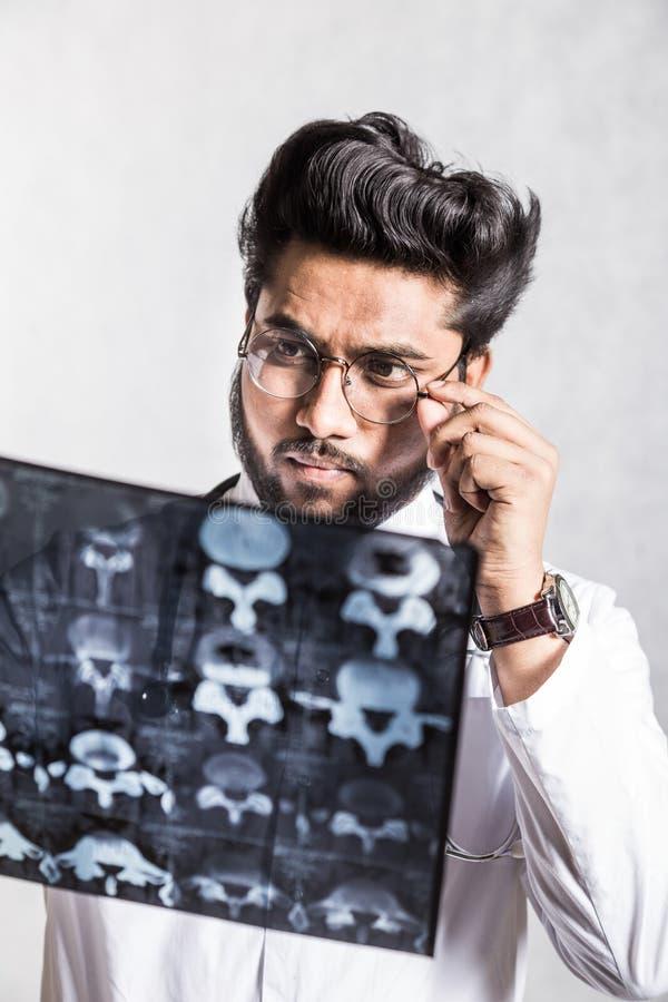 Le jeune docteur beau dans un manteau blanc avec un st?thoscope v?rifie attentivement le rayon X du patient photos libres de droits