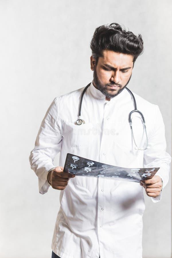 Le jeune docteur beau dans un manteau blanc avec un st?thoscope v?rifie attentivement le rayon X du patient photo stock