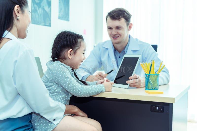 Le jeune docteur caucasien amical de pédiatre examine la fille patiente d'enfant avec sa mère, consultation avec un stéthoscop photographie stock libre de droits