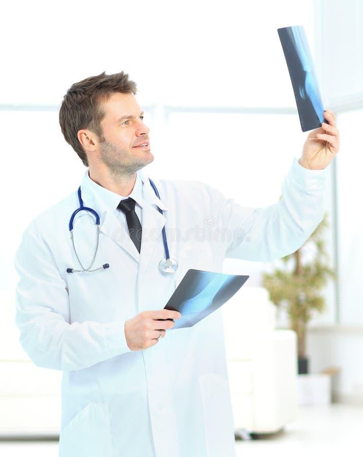 Le jeune docteur considèrent des photos de rayon X photo libre de droits