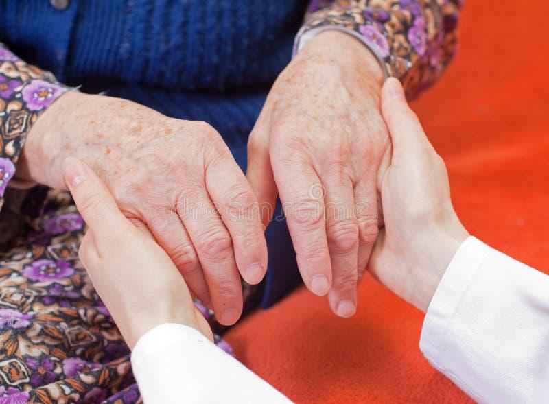 Le jeune docteur doux retient la main de dame âgée photos stock