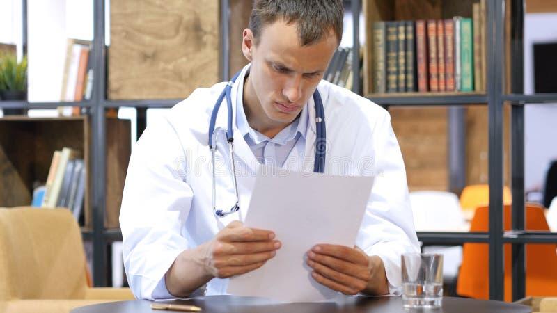 Le jeune docteur positif beau étudie le rapport médical dans sa clinique image libre de droits