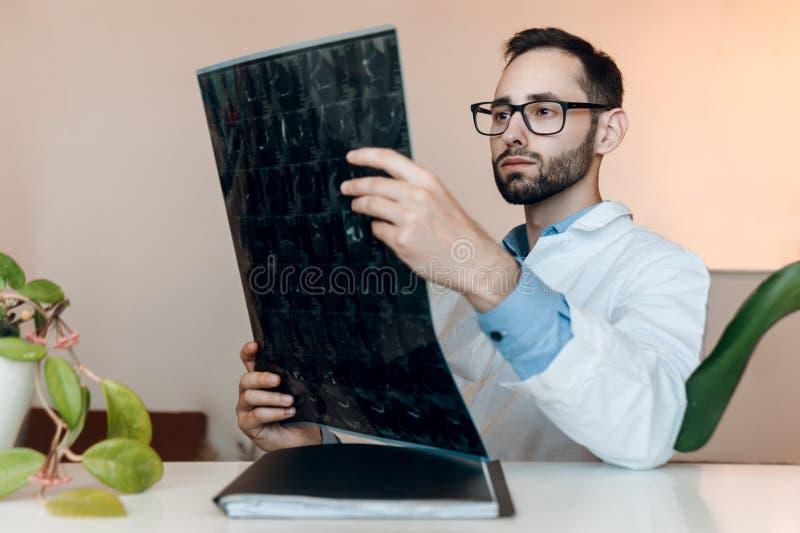 Le jeune docteur s'assied le coffret et en regardant la représentation de résonance magnétique tiré du genou-joint mri de blessur image stock