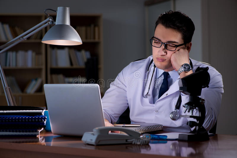 Le jeune docteur travaillant tard dans le bureau image stock