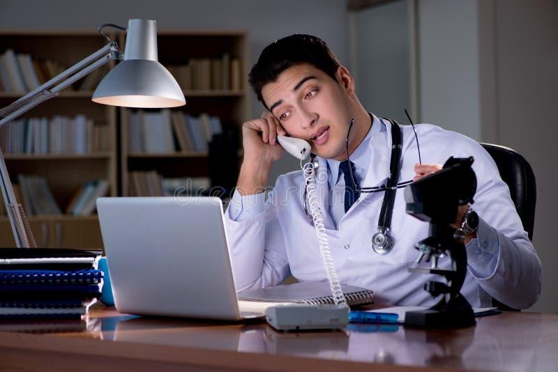 Le jeune docteur travaillant tard dans le bureau photographie stock libre de droits
