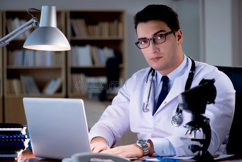 Le jeune docteur travaillant tard dans le bureau photographie stock