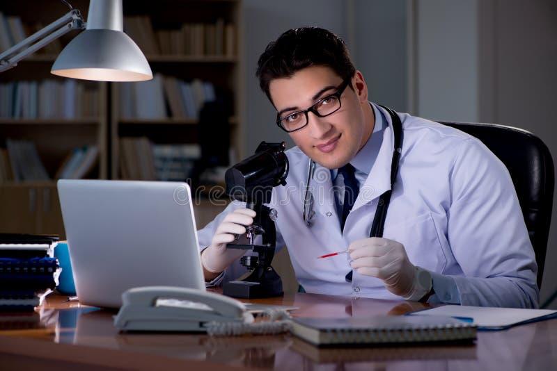 Le jeune docteur travaillant tard dans le bureau images libres de droits