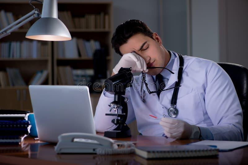 Le jeune docteur travaillant tard dans le bureau photos libres de droits