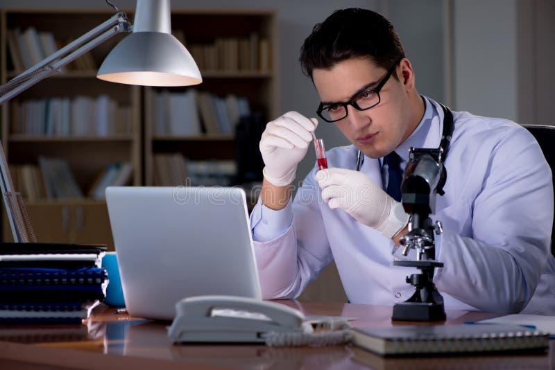Le jeune docteur travaillant tard dans le bureau photo libre de droits