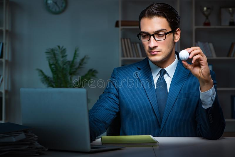 Le jeune employé avec la boule de golf dans le bureau photographie stock