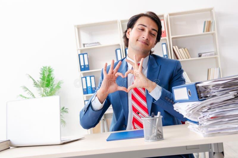 Le jeune employé masculin dans le concept drôle de bourreau de travail photos libres de droits