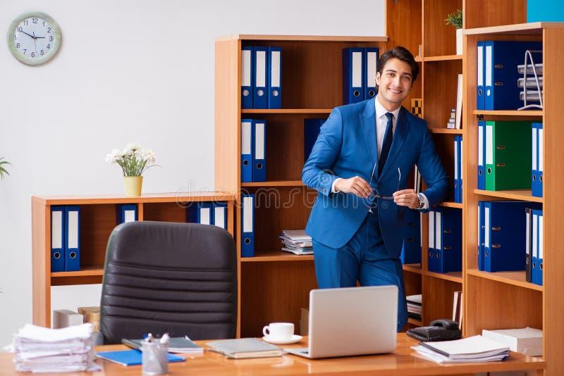 Le jeune employé travaillant dans le bureau photographie stock libre de droits