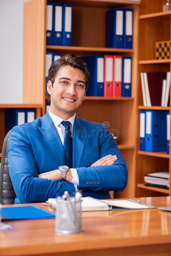 Le jeune employé travaillant dans le bureau photos stock