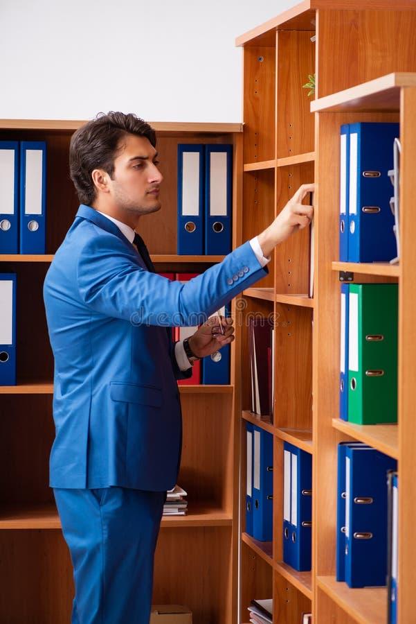 Le jeune employé travaillant dans le bureau photo stock