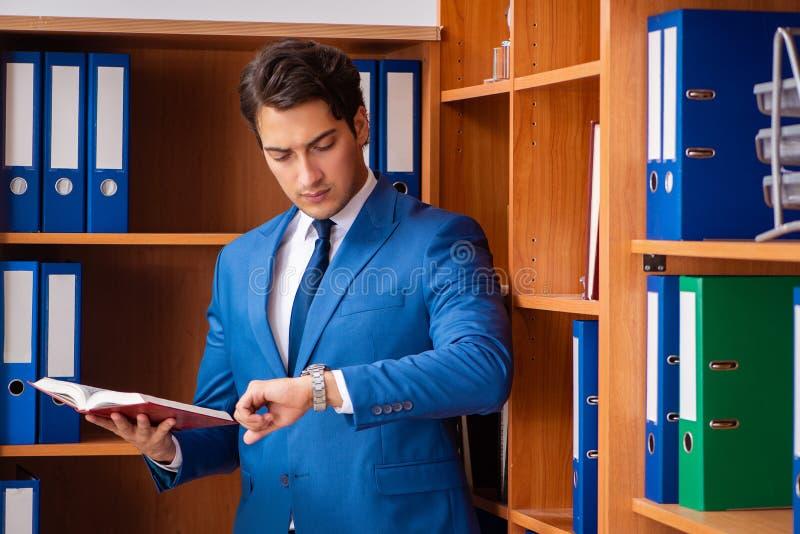 Le jeune employé travaillant dans le bureau photographie stock