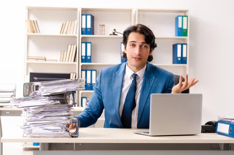 Le jeune employ? occup? bel s'asseyant dans le bureau photos libres de droits