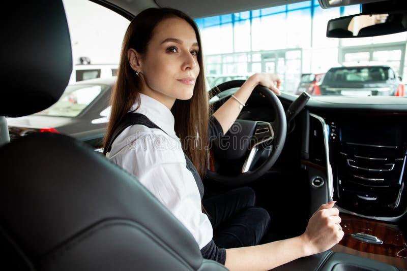Le jeune essai de femme d'affaires conduisent sa nouvelle voiture photos libres de droits