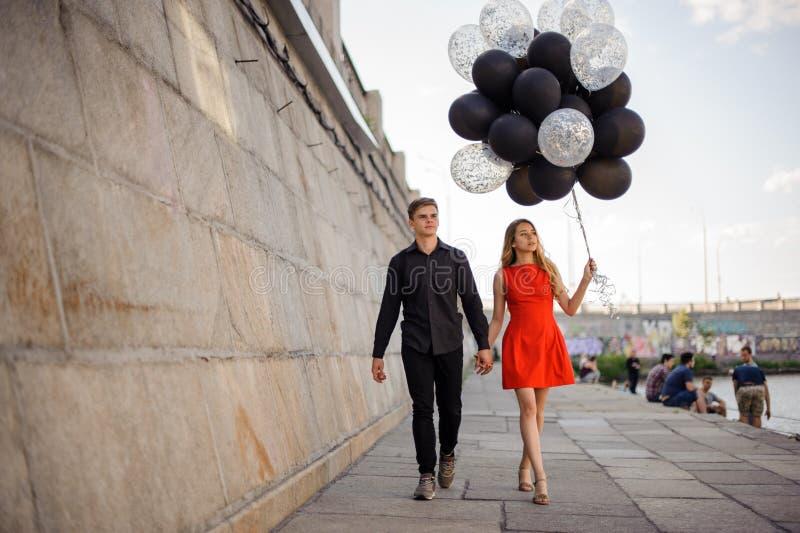 Le jeune et beau couple marche le long de la promenade images libres de droits