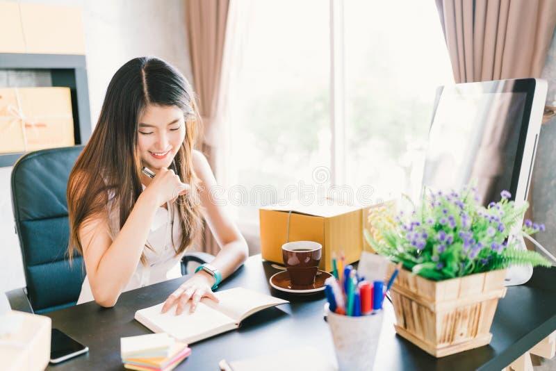 Le jeune et bel petit entrepreneur asiatique travaillent à la maison le bureau, organisant l'ordre d'achat La livraison d'emballa photographie stock