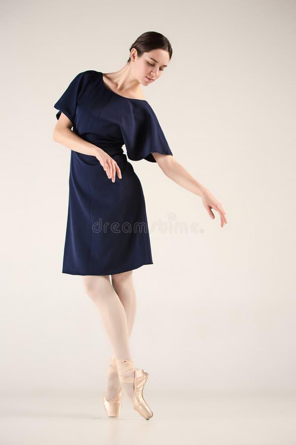 Le jeune et la ballerine incroyablement belle danse dans un studio bleu images libres de droits