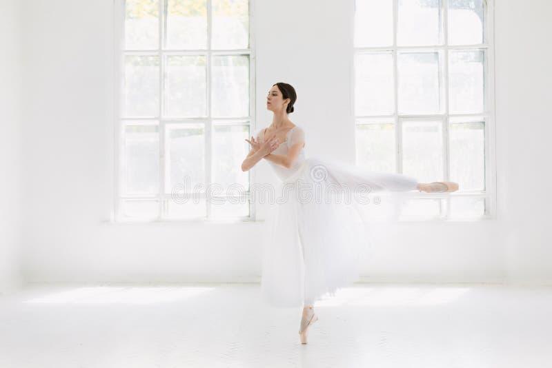 Le jeune et la ballerine incroyablement belle est posant et dansant dans un studio blanc photo stock