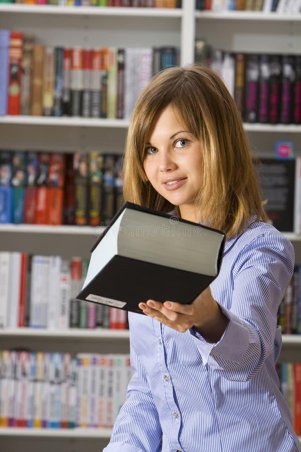 Le jeune femme étire le grand livre noir photos stock