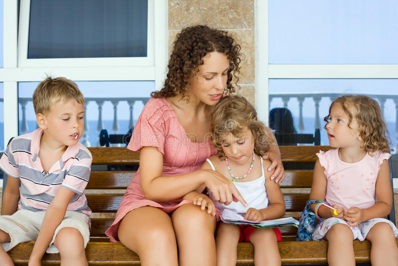 Le jeune femme affiche le livre à deux petites filles et à garçon image libre de droits