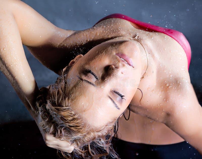 Le jeune femme apprécient dans des gouttelettes d'eau photos libres de droits