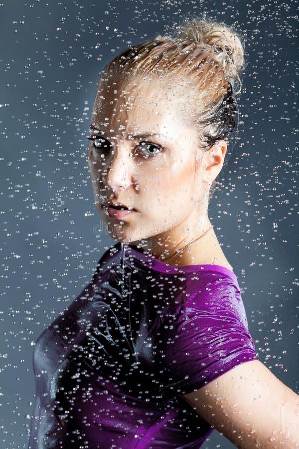 Le jeune femme blond dans l'eau éclabousse photographie stock libre de droits