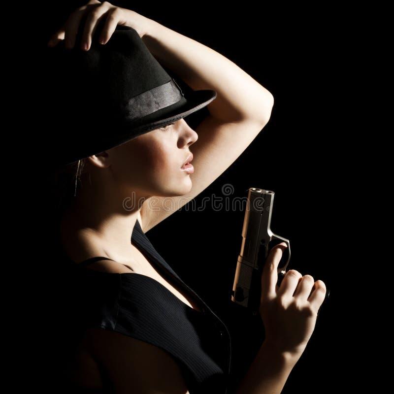 Le jeune femme dans un chapeau et avec un pistolet photo stock